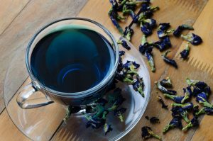 Glass cup of blue flower tea and dried flowers